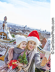 mother and child with cellphone taking selfie at Guell Park