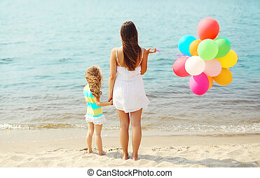 Mother and child with colorful balloons standing on beach near sea, view back