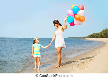 Mother and child with colorful balloons walking on beach near sea