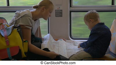 Mother and child with map traveling by train