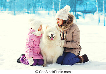 Mother and child with white Samoyed dog together on snow in winter day