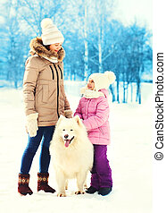 Mother and child with white Samoyed dog walking in winter day