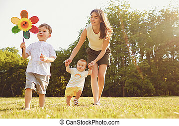 Mother and children are walking in the park at sunset.