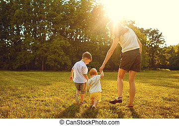 Mother and children are walking in the park at sunset .
