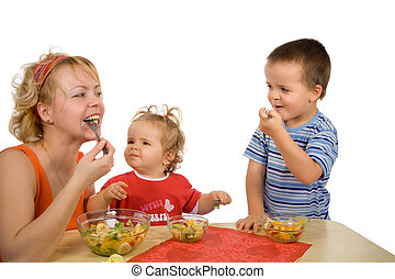 Mother and children eating fruit salad - Mother and children...