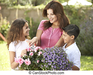 Mother And Children Gardening Together