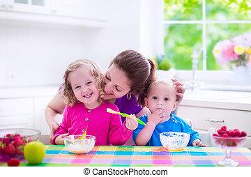 Mother and children having breakfast