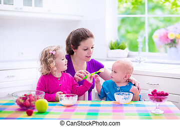 Mother and children having breakfast