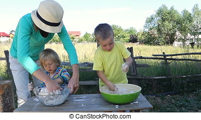 Mother and children making bread dough in nature