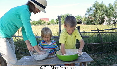 Mother and children making bread dough