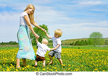 Mother and Children Playing and Dancing Outside in Flower ...