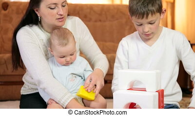 Mother and children playing with colored blocks building the house