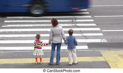 Mother and children, stand and wait to cross road at pedestrian crossing