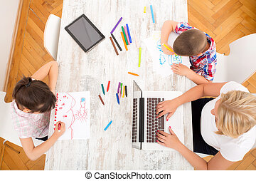 Mother and children with a laptop at home - A mother with...