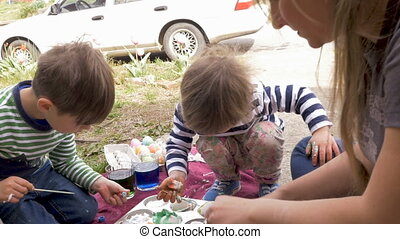 Mother and children working on an arts and crafts project together outside