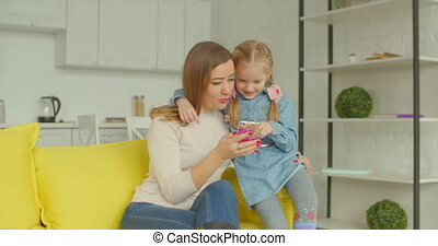 Mother and cute girl browsing online on cellphone - Positive...