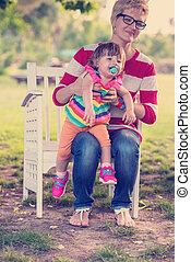 mother and cute little daughter sitting on wooden bench