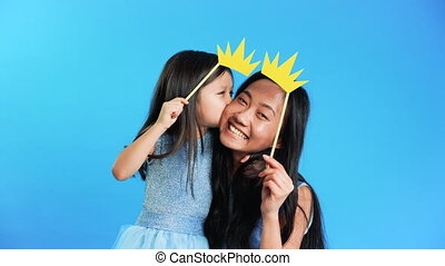 Mother and cute little daughter with a paper crown on stick ...