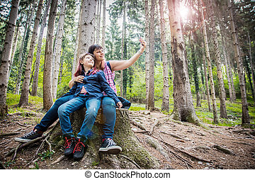 mother and daughter are doing selfie sit on the trunk of tree in a forest