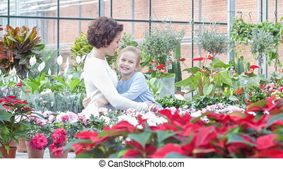Mother and daughter are hugging in the greenhouse.