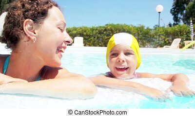 Mother and daughter are in the pool