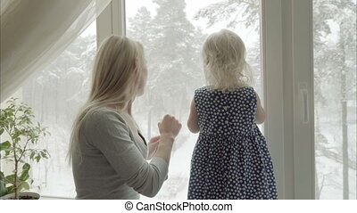 Mother and daughter are playing together on a windowsill,...