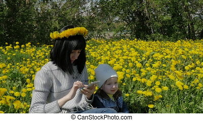 Mother and daughter are sitting in a park with beautiful dandelions. A woman writes sms from her phone.