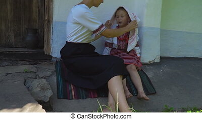 mother and daughter are sitting near the house - Mom and...