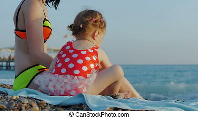 Mother and daughter are sitting on a beautiful beach and throw stones at sea. The concept of family, love, happiness, recreation and holiday.