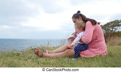 Mother and daughter are sitting on the beach
