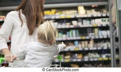 mother and daughter are walking around the grocery store.