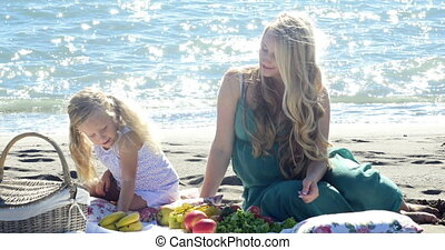 mother and daughter at a picnic on the beach