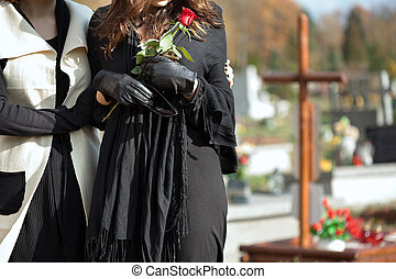 Mother and daughter at cemetery - Mother holding her...