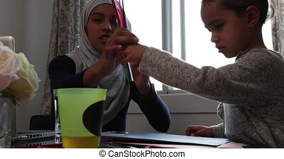 Front view of a young mixed race mother wearing hijab with her young daughter in the kitchen, sitting at a table, colouring together