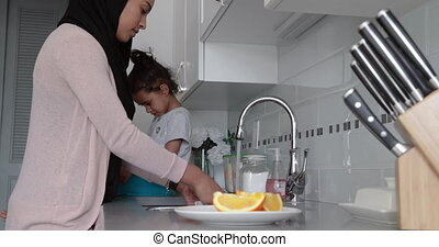 Mother and daughter at home - Side view of a young mixed ...