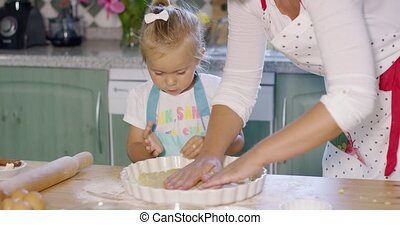 Mother and daughter baking a homemade pie standing together...