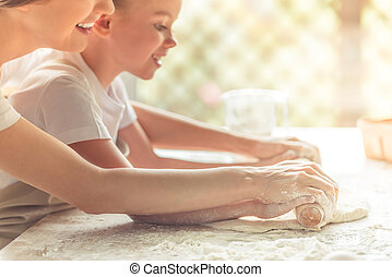 Side view of cute little girl and her beautiful mom in aprons smiling while flattening the dough using a rolling pin in the kitchen, cropped