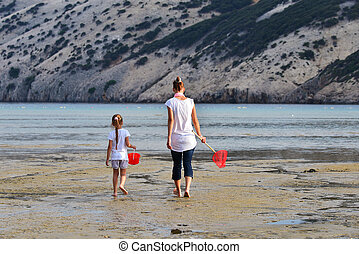 Mother and daughter be fishing nets in the sea