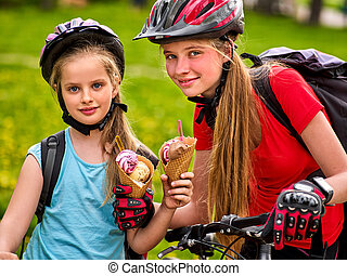 Mother and daughter bicycle. Family eating ice cream , ride bike .