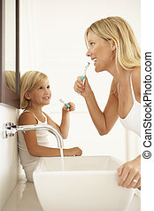 Mother And Daughter Brushing Teeth In Bathroom Together