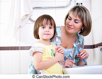 A young girl and her mother woke up early in the morning brushing his teeth in his bathroom