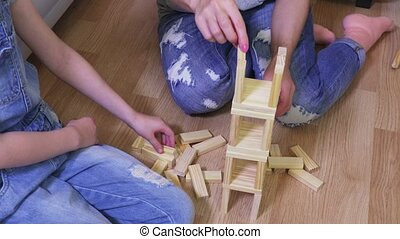 Mother and daughter build a tower of wooden blocks