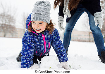 Mother and daughter building a snowman in winter nature