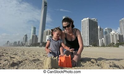 Mother and daughter builds sand castle in Surfers Paradise Australia