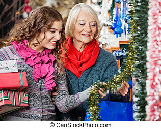 Mother And Daughter Buying Christmas Decorations - Beautiful...
