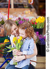 Mother and daughter buying tulips