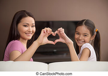 Mother and daughter. Cheerful mother and daughter gesturing and smiling while sitting in front of the TV