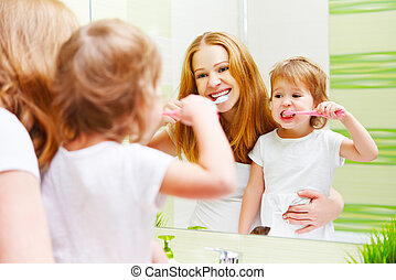 mother and daughter child girl brushing her teeth toothbrushes front of mirror