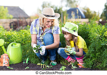 Mother and daughter child planting strawberry seedlings in summer