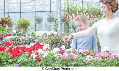 Selecting a flower. Daughter and her mother look fascinated by beautiful flowers then take one for themselves.